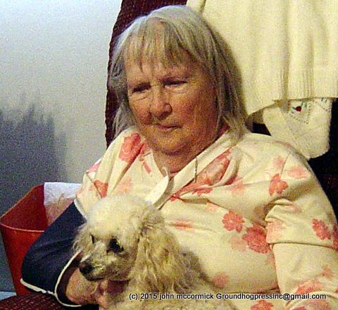 Photo of elderly woman holding lapdog.